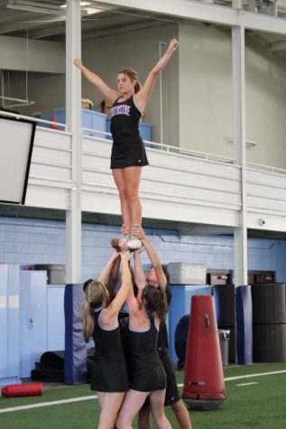 Cheer team practices for football game performance.