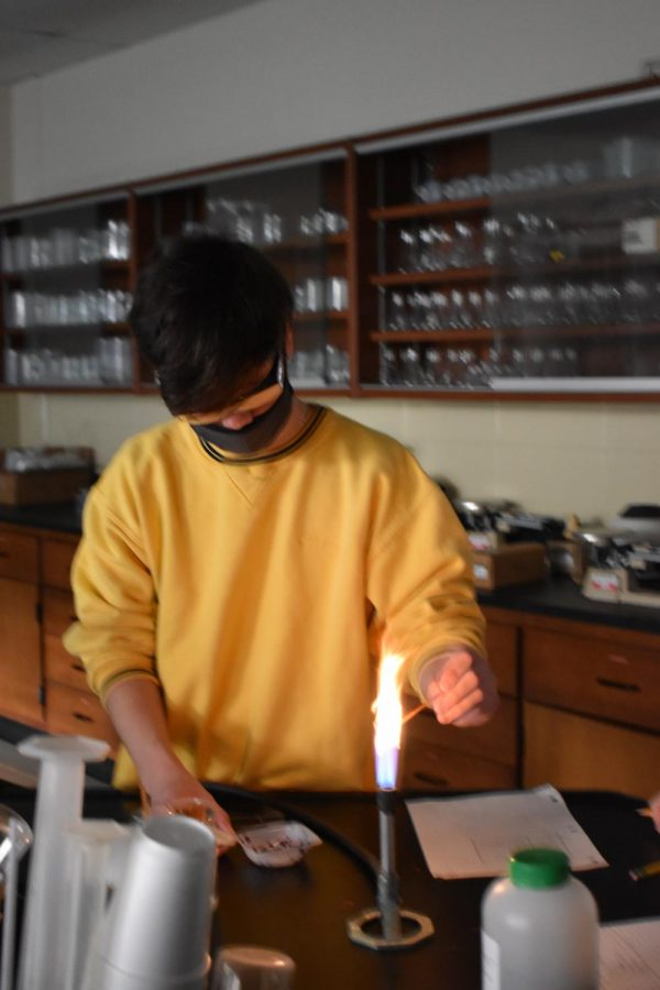 Andrew Ross participates in chemistry flame lab.