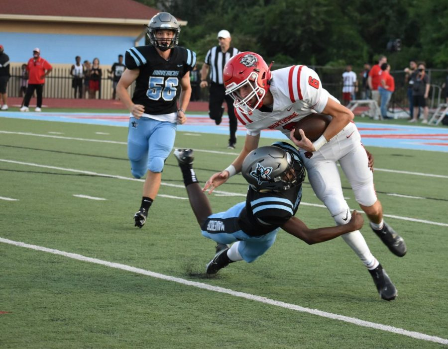 Strong safety Devin Huggins takes down quarterback Walker Catsavis during the first quarter of the home opener.